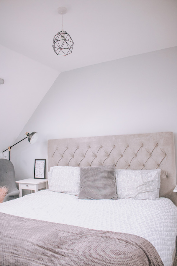 Jodie's master bedroom is neat, organised and tidy and has a grey wall, a grey super king size bed with white and grey bedding.