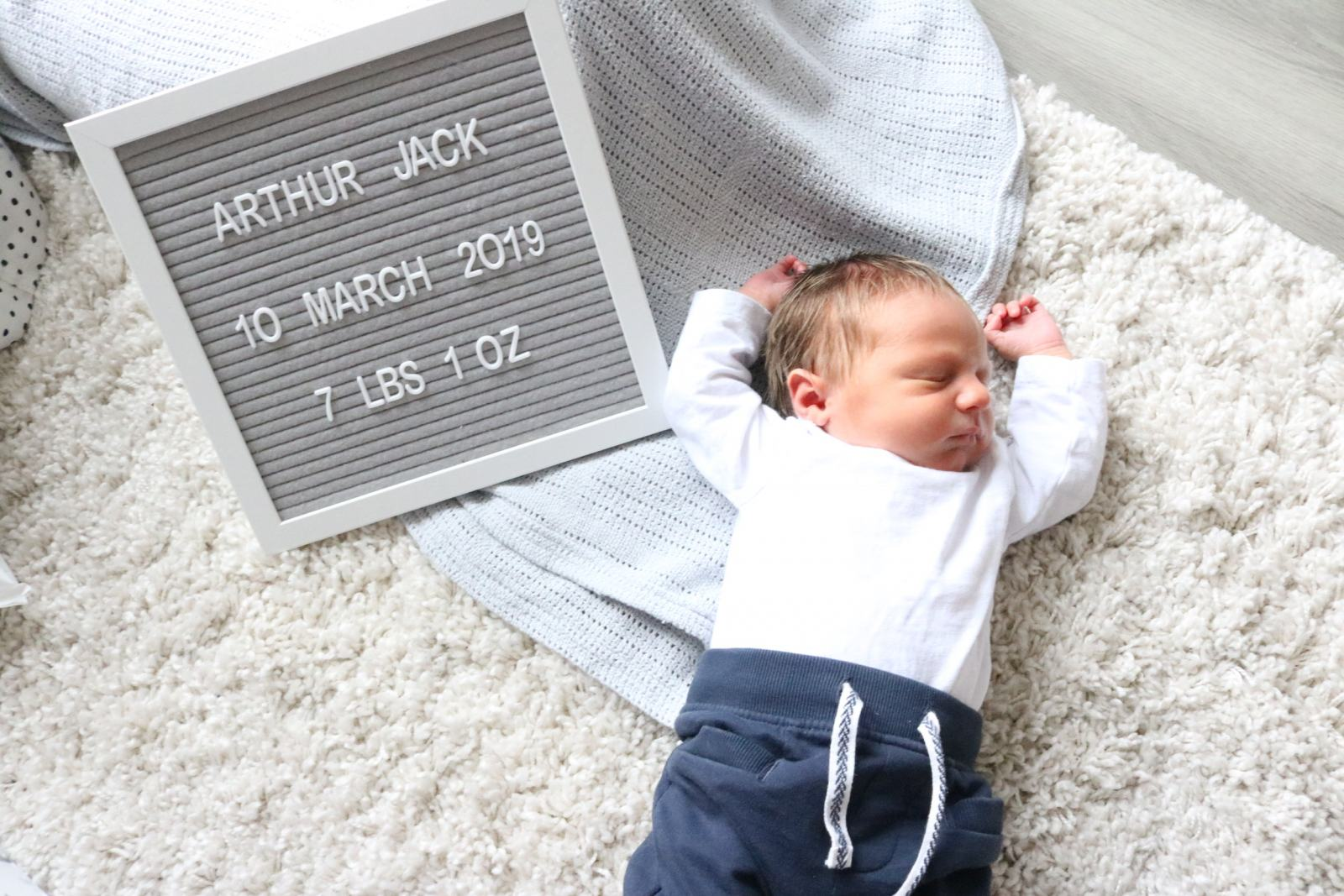 A Newborn baby named Arthur laying on a cream shaggy rug next to a sign with his date of birth and weight.