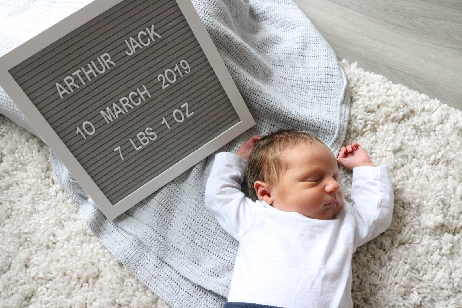A Newborn baby named Arthur laying on a cream shaggy rug next to a sign with his date of birth and weight