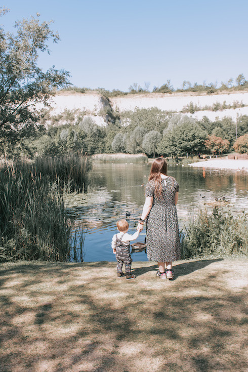 Jodie and Arthur are holding hands looking over the Bluewater Lake at The Bluewater Nature Trail.