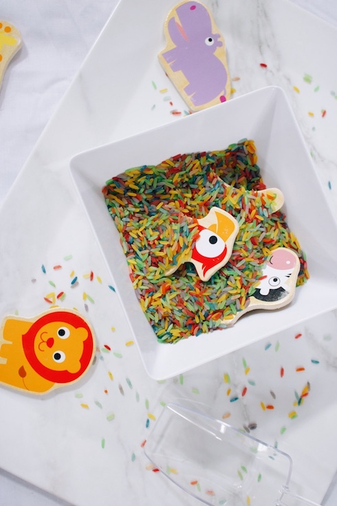 A rainbow rice play idea - wooden puzzle pieces hidden in a bowl of rainbow rice