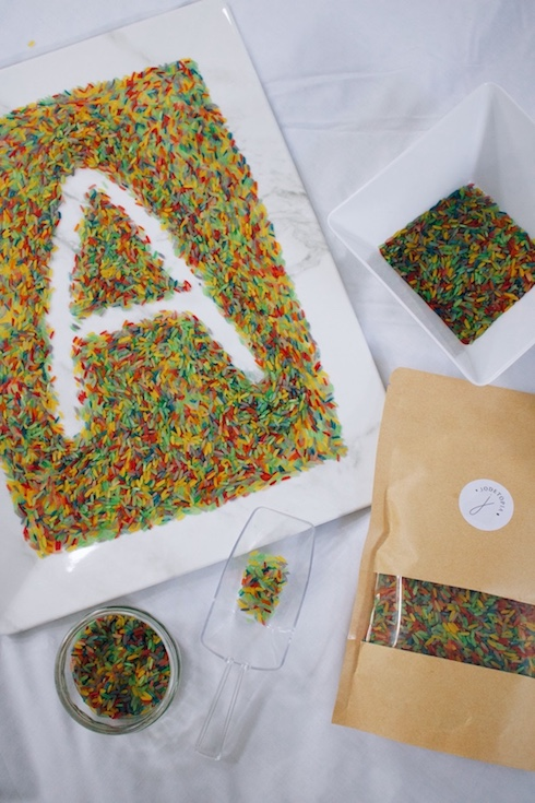 A rainbow rice play idea - writing practice in a tray of thinly scattered rainbow rice