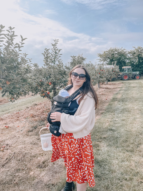 A woman standing in a PYO apple orchard as she has gone apple picking in Kent with her toddler